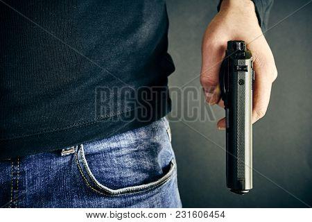 The Man With Gun In Hand On Dark Background