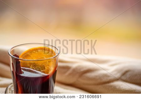 Stilllife With Glass Of Hot Dark Drink With Cinnamon And Orange On Beige Background