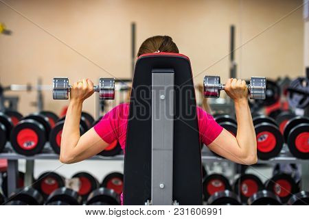 Back view of a young woman holding dumbbell and trainig deltoid in modern gym poster