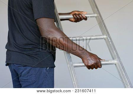 An Electrician Holds An Aluminum Ladder. The Builder Carries An Aluminum Stepladder On Gray Backgrou