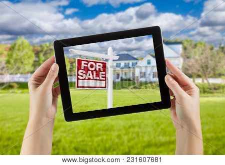 Female Hands Holding Computer Tablet with Home For Sale Sign on Screen, House Behind.