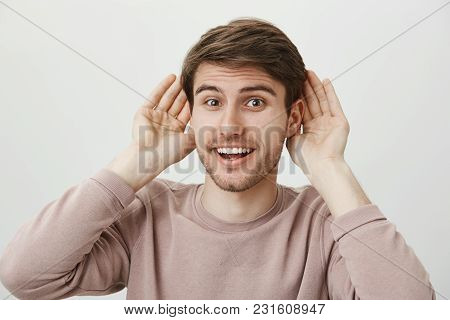 Ready To Receive New Information. Studio Portrait Of Attractive Positive Guy Holding Palms Near Ears