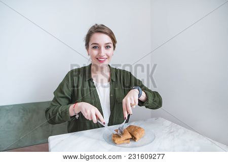 Beautiful Girl Sitting In A Restaurant And Eating A Sandwich With A Knife And Fork. Lunch In A Light