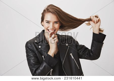 Saying Goodbye To Split Ends. Studio Shot Of Pleased Happy Young Woman Pulling Hair With Hand, Smili