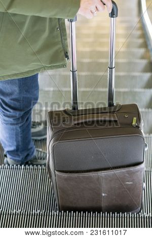 Man Traveling By Airplane. Hand Of The Passenger With Luggage On The Escalator At The Airport