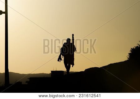 The Fisherman Returns Home After A Day Of Fishing Silhouetted Against The Sky