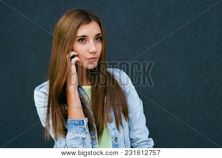 A Girl On A Dark Background Sticks In The Phone, Smiles, Brunette, Lots Of Space For Inscription
