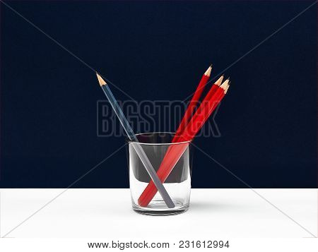 Red pencils photo mockup Set of identical red pencils and one gray pencil are standing in glass against blue wall background on white desk Template with space for text