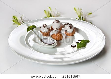 Dessert Eclairs On A White Dish Decorated With Mint