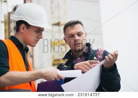 Engineering, Architecture, Investments, Building Concept. Boss Shows Project To Engineer With Seriou