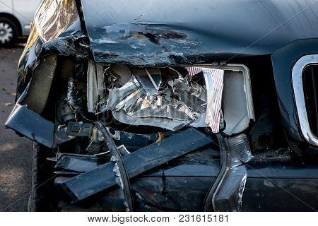 Detail Of A Broken Headlamp On A Dark Blue Car After Traffic Accident