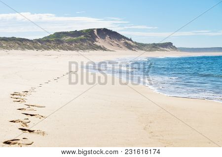 Footsteps At The Beach With Green Hills Of Peterborough At The Great Ocean Road, Victoria, Australia