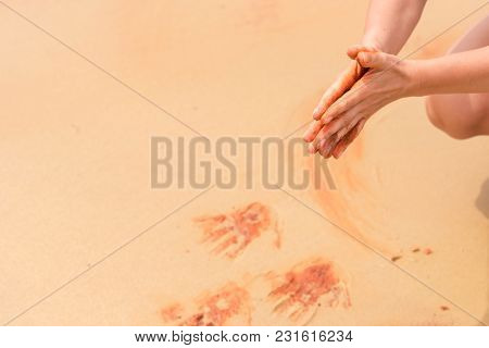Woman Hands Creating Shapes With Red Sand On The Beach In Aboriginal Art Style