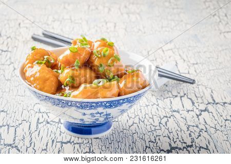 Bowl Of Oriental Lemon Chicken Garnished With Thinly Sliced Green Onion.