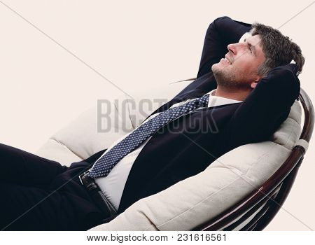 side view. Businessman thinks, sitting in a comfortable chair