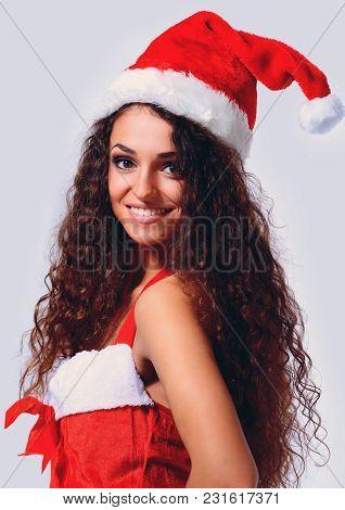 Portrait of beautiful brunette woman wearing santa claus clothes