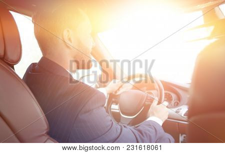 businessman sits at the wheel in his car and looks at the road