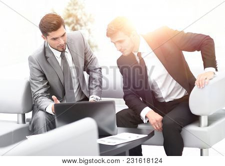 two colleagues working on a laptop sitting in the lobby of the office.