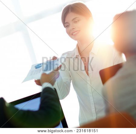 senior Manager, handing the employee a document with financial data.