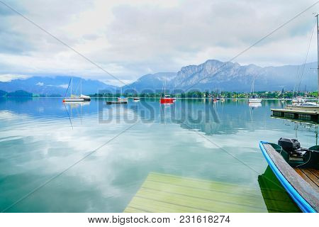 Moored Boats Float Lazily On Calm Natural And Beautiful Alpine Lake Mondsee Surrounded By Austrian A