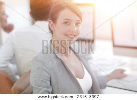 rear view. beautiful business woman sitting near the desktop and looking at the camera.