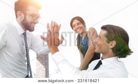 business colleagues giving each other high five.