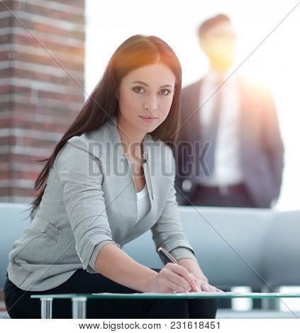 business woman signs documents in a modern office.
