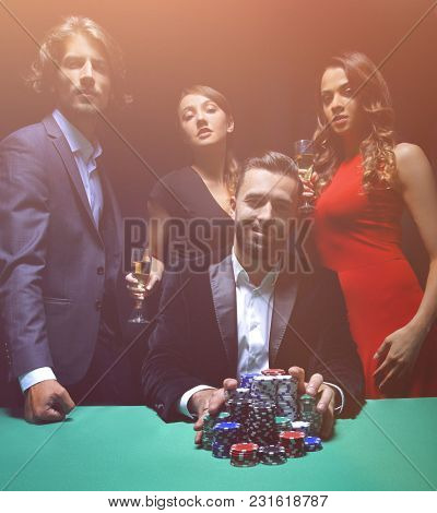 People standing at the table, looking, while a person is betting
