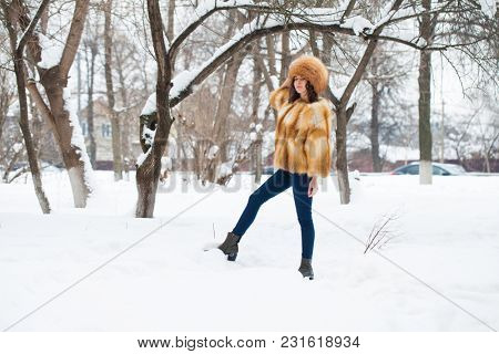 Young beautiful girl in a fur hat and a red fox fur coat posing against a winter park background