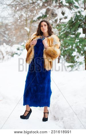 Young beautiful brunette girl in blue fur coat posing on winter park. Model wearing stylish warm clothes.