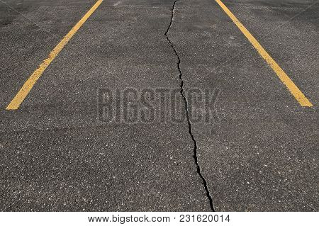 A Crack Runs Through A Marked Asphalt Parking Stall In A Parking Lot.