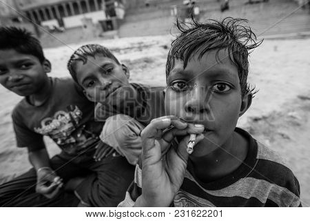 VARANASI, INDIA - MAR 16, 2018: Unidentified indian child seller of cane juice sits near the juicer on the street. According to legends, the city was founded by God Shiva about 5000 years ago.