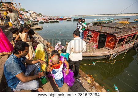 VARANASI, INDIA - MAR 16, 2018: Pilgrims on the banks of the Holy Ganga river. Varanasi is one of the most important pilgrimage sites in India and is one of the 7 sacred cities of Hinduism.