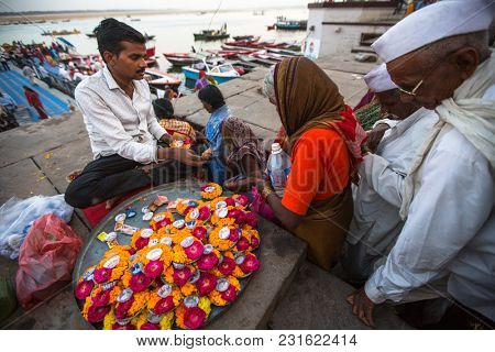 VARANASI, INDIA - MAR 17, 2018: Street seller on the banks of the sacred Ganges river selling flower petals, and small garlands for Hindu devotees to use in their devotions.