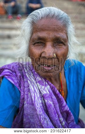 VARANASI, INDIA - MAR 13, 2018: Hindu woman pilgrim on the banks of Ganga river. Varanasi is one of most important pilgrimage sites in India and is one of the 7 sacred cities of Hinduism.