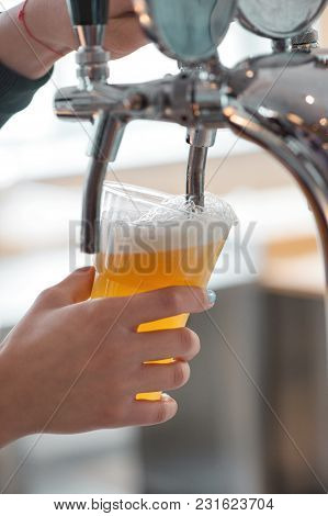 Plastic Cup Of Beer Flowing From Beer Tap With Nice  Foam Close-up In Female Bartender Hands On Blur