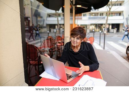 lady sitting in outdoor cafe and have conversation  with sister via laptop. Sisters not communicate for long time and woman very happy. Female smiling  waving,  blows air kiss and showing heart from hands. poster