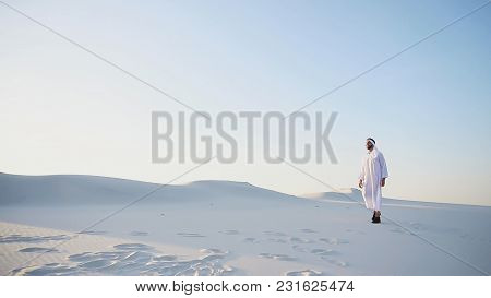 Handsome Young Muslim Driving Along Bottomless Desert And Looking Toward Sunset, Admiring Beauty Of