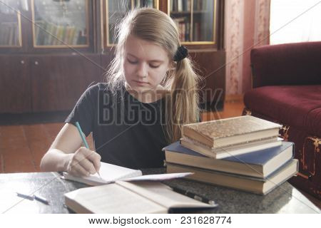 Portrait Of A Girl Teen Doing Lessons At Home, Close Up