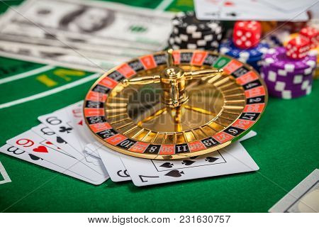 Casino Roulette. Poker Chips On Table In Casino. Cards On Green Felt Casino Table