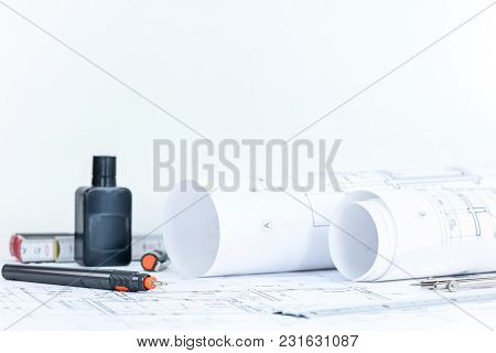 Blueprint Rolls, Project Plans, Engineering Drawing Tools On Wooden Desk. Architectural Workplace.