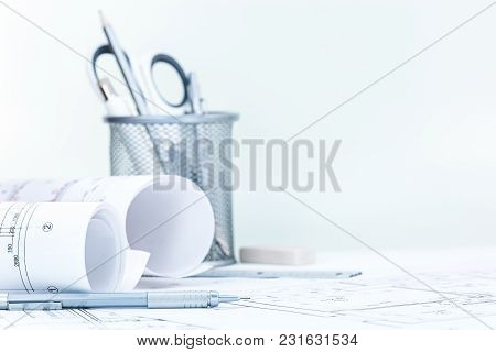 Engineering Project Plan With Blueprint Rolls, Pencil, Stationary Set On Architect Desk