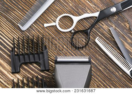 Comb, Scissors, Razor And Hair Clipper Lie On A Brown Wooden Table