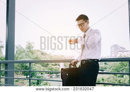 Young Asian Male Standing Checking Time And Holding Briefcase With Confident Looking At Watches On H