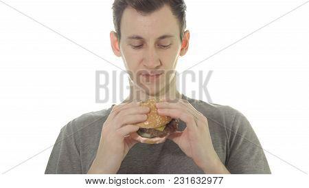Young Man Eats A Burger, Unhealthy Food.