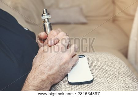Electronic Cigarette In The Hands Of A Man Who Sits In A Chair With A Mobile Phone. Copy Space. Clos