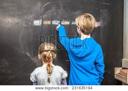Boy Explaining And Girl Something On The Chalkboard.