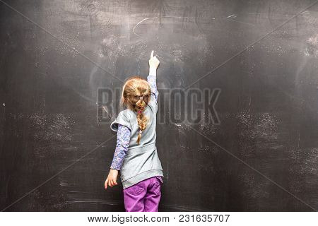 Back View Of A Little Girl Ponting To Something On A Chalkboard.
