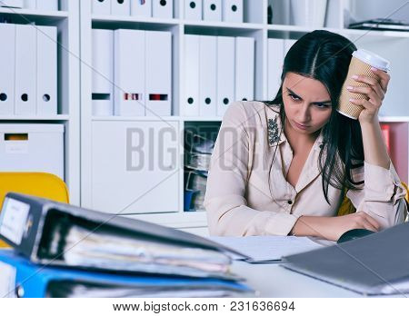 Tired And Exhausted Woman Looks At The Mountain Of Documents Propping Up Her Head With Her Hands. Hu