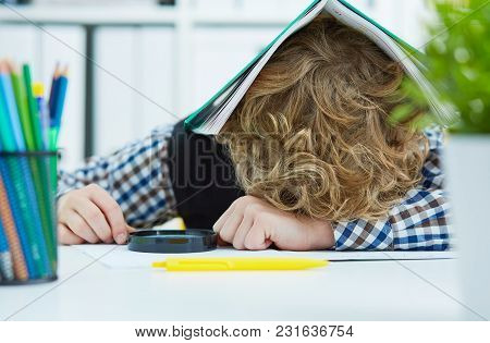 Tired Schoolboy Is Sitting At A Desk With Head On The Tablewith The Notebook On The Head. Large Numb